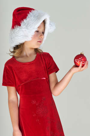 Little girl in red dress with red christmas ball Stock Photo - 606153