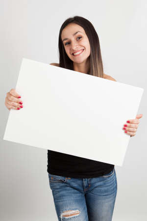 white sheet: Young brunette woman holding a white board