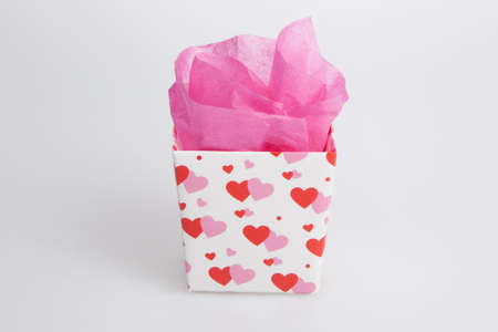 parer: Small Valentine gift box with pink parer on a white background