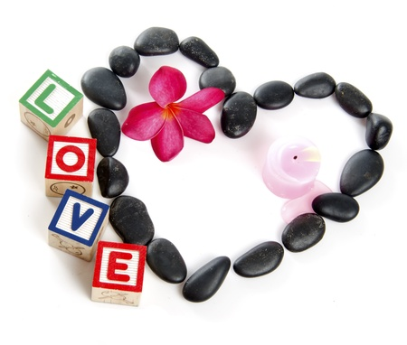 Love decorated by stones with fragipani flower, candle and wooden block letters   photo