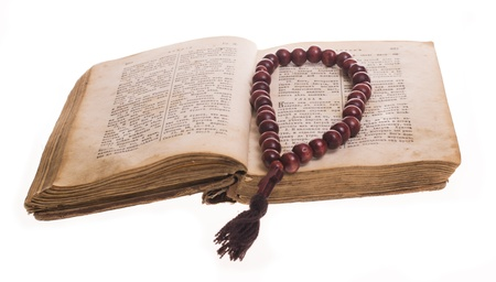 Open old bible and wooden rosary photo