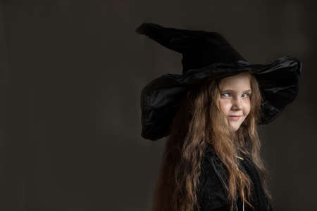Litlle girl in halloween witch costume on gray background