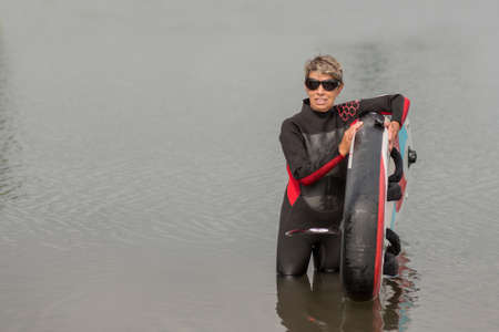active woman 65 years in wetsuit with surf standing in the water