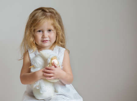 Redhair girl with snowman and angel on light gray background