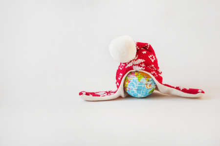 Globe in winter hat. Christmas minimalism concept