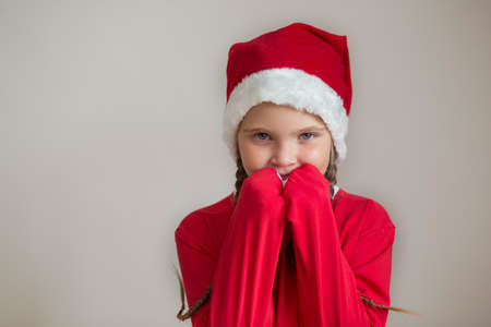 Happy girl in santa costume with hands near her face on light gray background