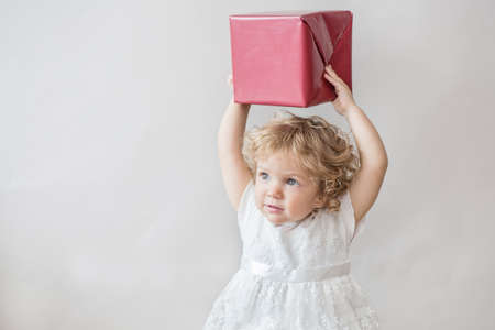 Happy curly girl in white dress with Christmas gift on light gray background