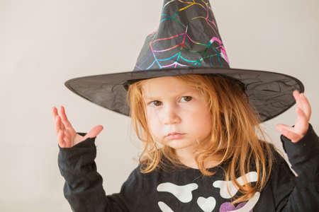 Emotional toddler girl in halloween witch costume on gray background