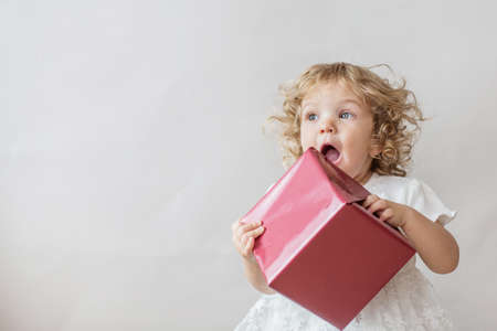 Excited curly girl in white dress with Christmas gift on light gray background