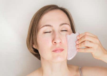 European woman applying guasha massage close up portrait
