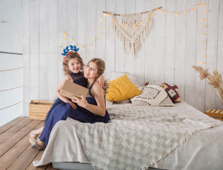 Mother and daughter in beautiful blue dress sittig on bed with gift