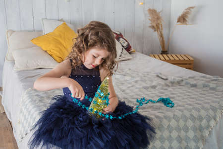 Little girl in blue dress decorating little Christmas tree sitting on the bed
