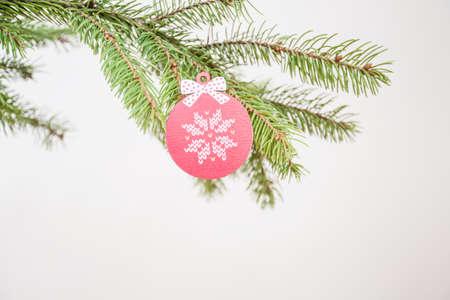 Wooden Christmas ornament on fir tree branch. Stockfoto