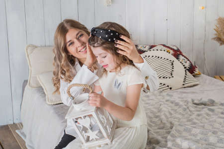 Mother and daughter sittig on bed with lattern for candle