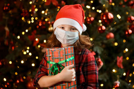 Girl in Santa hat and medical mask near Christmas tree with gift