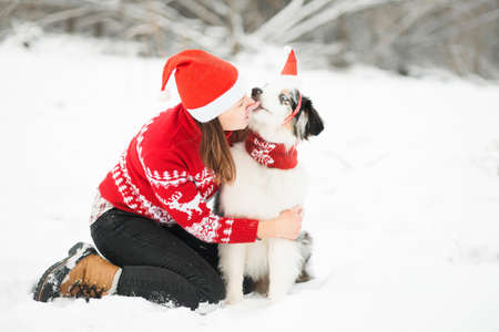 Australian shepherd in santa hat kissing woman in winter forest Stock Photo