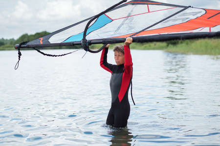 active woman 65 years in wetsuit with sail standing in the water