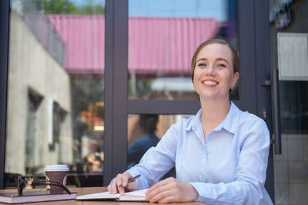 Portrait of happy business young woman, smiling while sitting in caffe and work.