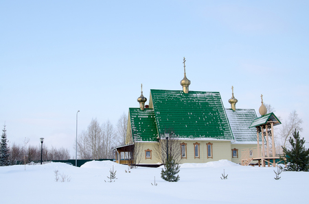 the place is important: Picturesque blue Orthodox Church on a forest clearing, covered with the snow. Winter scenery. Important place of worship in small village Koterka, east part of Poland. Stock Photo