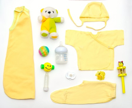 teteros: top view of baby girl yellow clothes and toy stuff, baby fashion concept Foto de archivo
