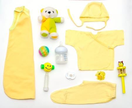 teteros: vista desde arriba de la ropa amarilla del bebé de juguete y otras cosas, el concepto de la manera del bebé
