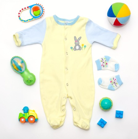 stuff toy: top view of baby boy yellow-blue clothes and toy stuff, baby fashion concept