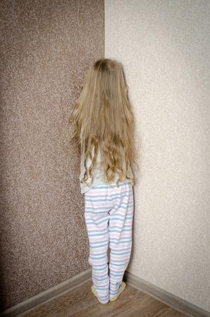 petite fille triste: M�chante petite fille est debout dans le coin puni � la maison Banque d'images