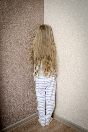 naughty child: Naughty little girl is standing in the corner punished at home