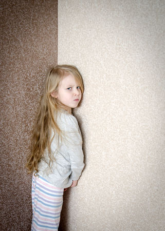 home corner: Naughty little girl is standing in the corner punished at home
