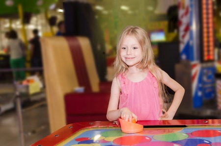 amusment: little girl standing and playing air hockey at indoor amusement park