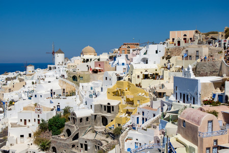 Beautiful view with traditional white buildings over the village of Oia at the Island Santorini, Greece