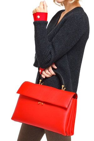 Girl holds a red ladys bag close-up on an isolated white background