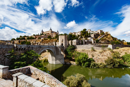 Panoramic view of Toledo Spain on a sunny summer day. Ancient stone walls and houses, blue sky and red-hot earth.