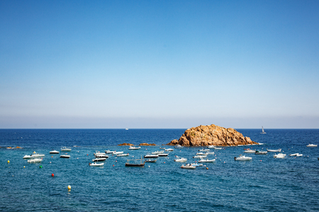 Rock in the Gulf of Tossa de Mar. Yachts in the bay. Cloudless sky and calm sea
