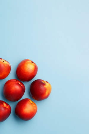 A few ripe red nectarines on a blue background Stock Photo