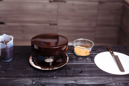 Glaze chocolate cake. The confectioner is a young woman, glazes a cake and garnishes it with gold.