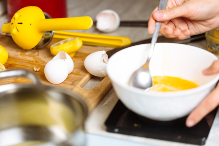 The confectioner whipped eggs in a white bowl Stock Photo