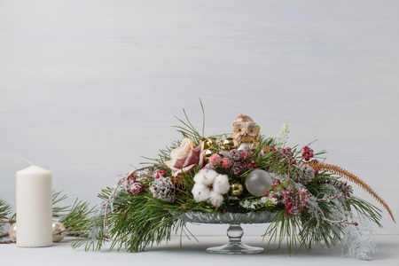 Decorative Christmas bouquet with candles. In a glass vase with fir branches on a light background Stock Photo