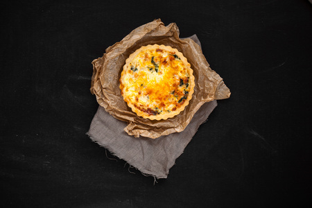 kish with onions and cheese. cheese cake. on a fabric and a black background. 免版税图像
