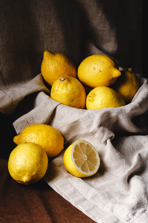still life with lemons in a dark style. ripe yellow lemons in the bowl, cinnamon tissues and deep shadows. half a lemon in the foreground