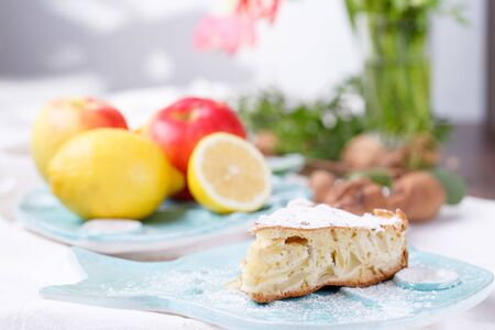 close up apple pie on a blue plate. lemon with apples in a blue plate in the background. light background