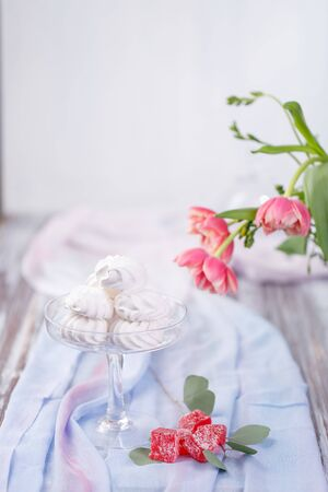 marshmallows in a glass stand and red marmalade on a blue fabric. red roses in the background. light background