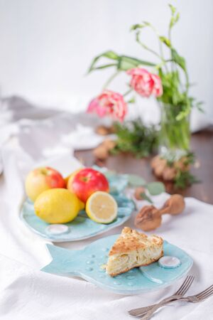 apple pie on a blue plate. lemon with apples in a blue plate in the background. red roses on a light background Stok Fotoğraf