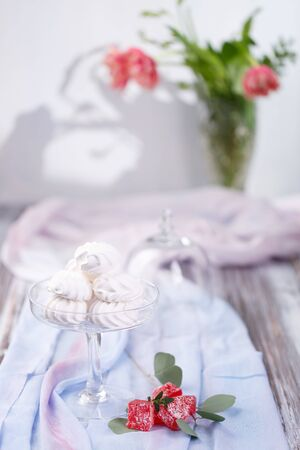 marshmallows in a glass stand on a blue fabric. red roses in the background. light background