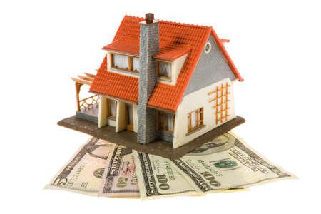 Miniatuur huis met dollars geïsoleerd op witte achtergrond