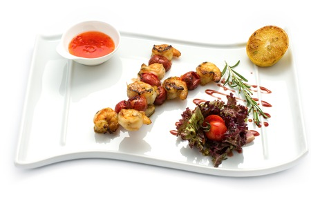 Roasted shrimp tails on the skewer with lettuce, lemon and soy sauce Stock Photo
