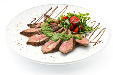 sliced veal steak medium rare with sauce on a white plate, white background Stock Photo