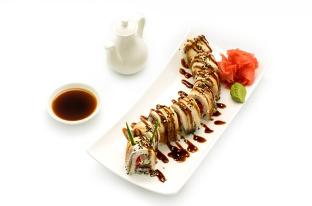 Golden dragon sushi roll is served on a white plate, white background with wasabi and ginger