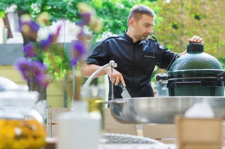grill tongs sausage: Male cook some barbeque prepares on the restaurant terrace. Close to the road. Stock Photo