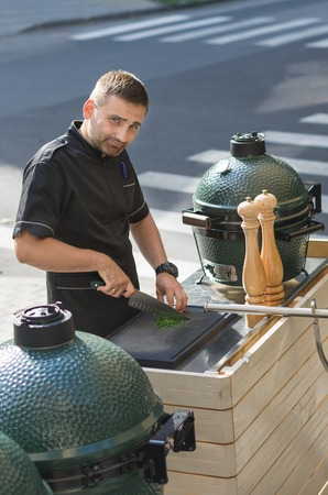 Male cook some barbeque prepares on the restaurant terrace. Close to the road. Stock Photo